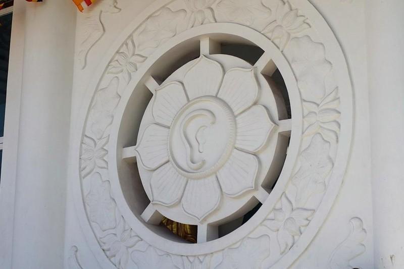 """Hai bên cửa chính có hai ô cửa hình hoa sen mang một mắt và một tai nằm trong bánh xe Phật pháp, mang hàm ý """"Nhất tâm nghe, thấy, ngay đấy thấy Phật""""."""