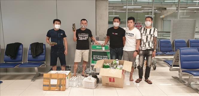 Nhóm công dân Việt Nam bị mắc kẹt tại sân bay Survanabhumi tiếp nhận thức ăn và đồ dùng thiết yếu do cán bộ Đại sứ quán chuyển đến. Ảnh: TTXVN phát