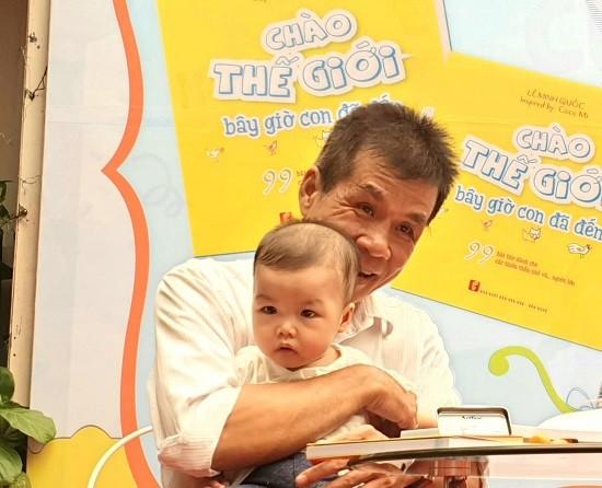 Nhà thơ Lê Minh Quốc và con gái nhỏ trong buổi ra mắt sách Chào thế giới bây giờ con đã đến. Ảnh: NXB