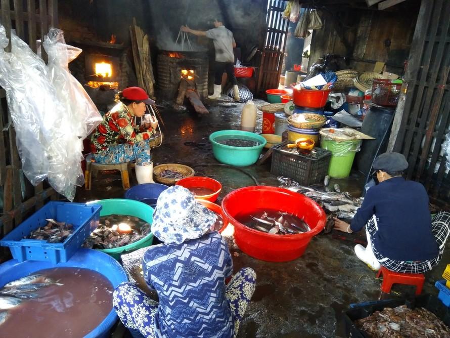 Những người thợ hấp cá ăn vội buổi sáng ngay tại lò hấp. Ảnh: Vân Phi