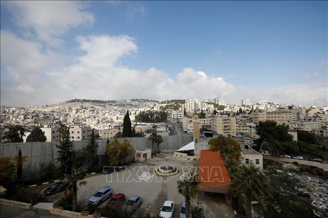 Bức tường ngăn cách khu vực Đông Jerusalem (trái) và ngôi làng Abu Dis của người Palestine. Ảnh: AFP/TTXVN