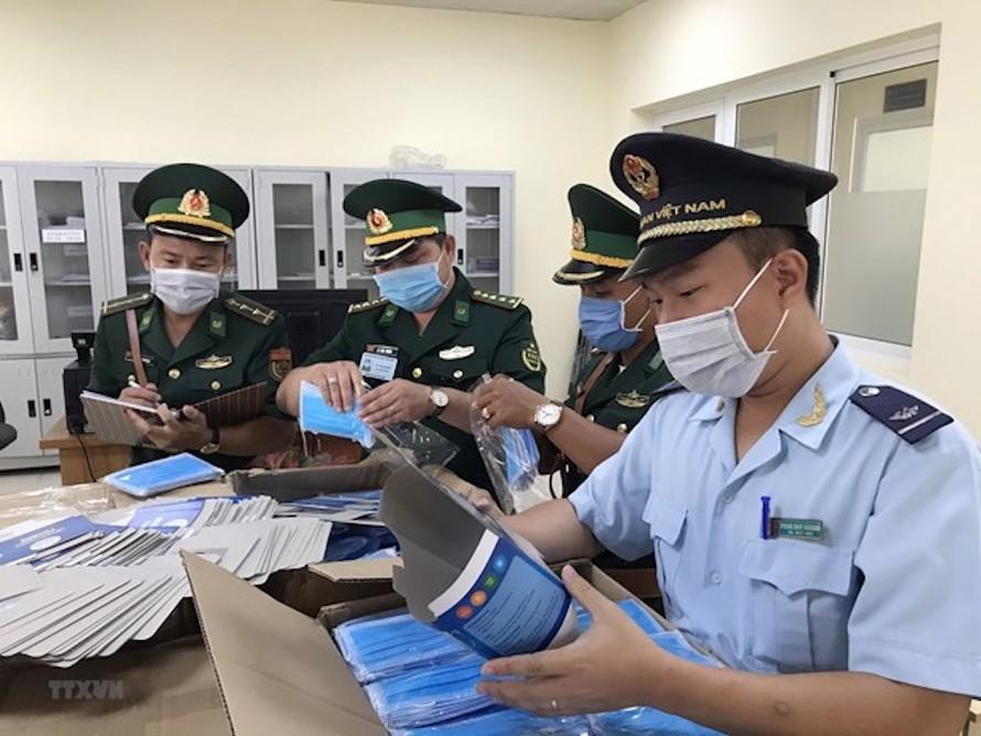 Lực lượng chức năng kiểm đếm số khẩu trang bị thu giữ. (Ảnh: Công Mạo/TTXVN)