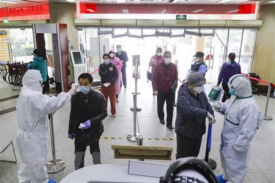 Kiểm tra thân nhiệt cho bệnh nhân tại một bệnh viện ở Vũ Hán, tỉnh Hồ Bắc, Trung Quốc. (Ảnh: THX/TTXVN)