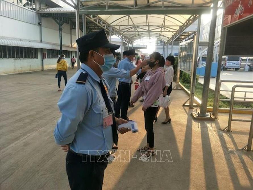 Kiểm tra thân nhiệt cho công nhân trước khi vào ca tại Công ty TNHH Grand Gain tại KCN Đồng Xoài II, tỉnh Bình Phước. Ảnh: Dương Chí Tưởng/TTXVN