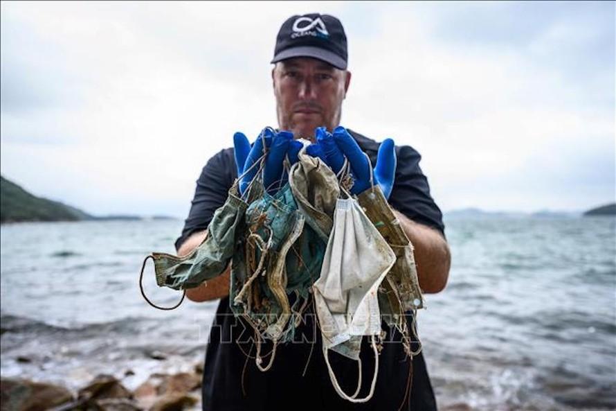 Chuyên gia tổ chức bảo vệ môi trường OceansAsia thu nhặt khẩu trang dùng một lần trên bãi biển vùng đảo Lantau, Hong Kong, Trung Quốc. Ảnh: AFP/TTXVN