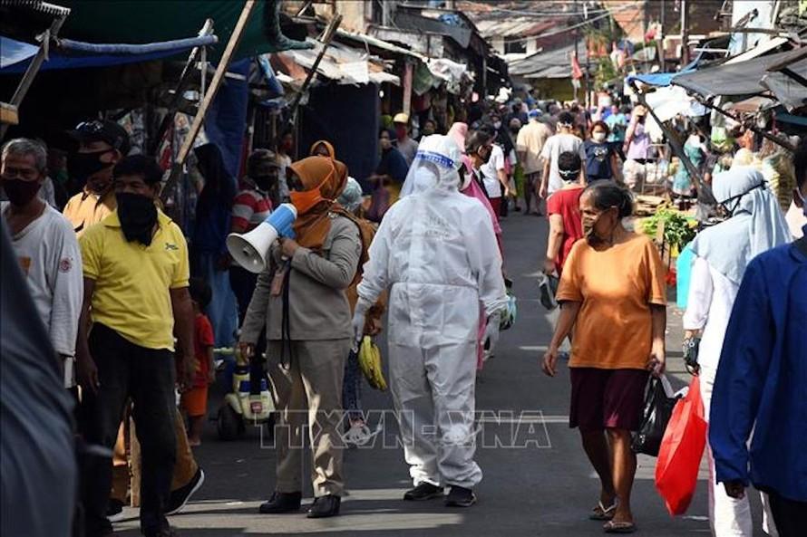 Nhân viên y tế kêu gọi người dân xét nghiệm COVID-19 tại một khu chợ ở Jakarta, Indonesia ngày 2/6/2020. Ảnh minh họa: THX/TTXVN