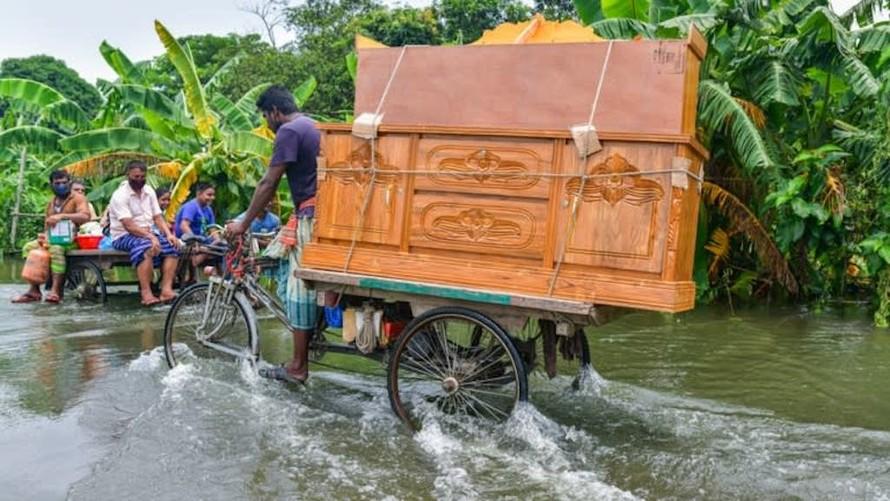 Một người đàn ông lội xe qua vùng nước lũ gần thủ đô Dhaka của Bangladesh.
