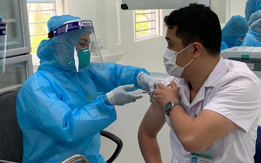 Một cán bộ y tế ở tuyến đầu chống dịch được vaccine phòng COVID-19.