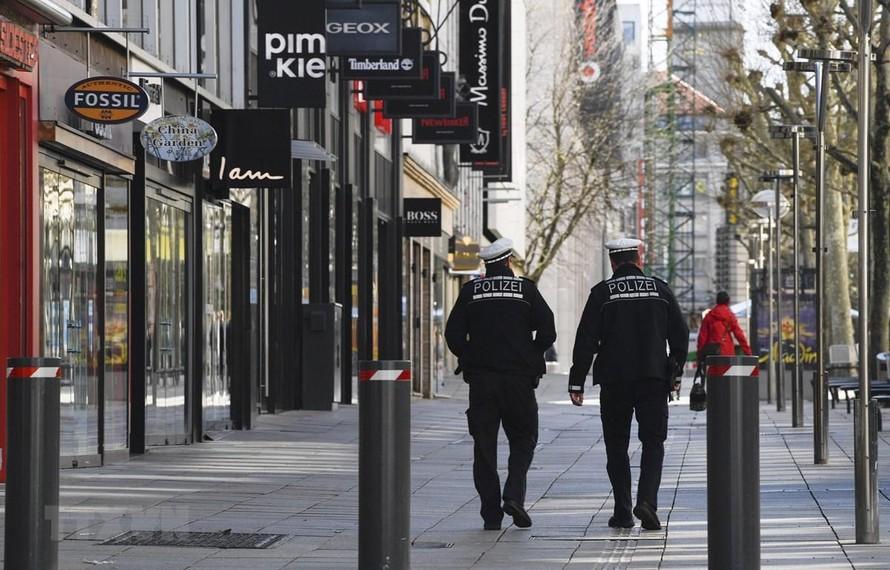 Nhân viên an ninh tuần tra gần Koeniggstrasse, một khu phố thương mại sầm uất ở Stuttgart, miền Nam Đức trong bối cảnh lệnh hạn chế được ban bố do dịch COVID-19.