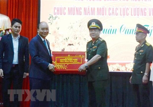 Thủ tướng Nguyễn Xuân Phúc tặng quà Tết cho cán bộ, chiến sỹ Công an thành phố Đà Nẵng. (Ảnh: Quốc Dũng/TTXVN)