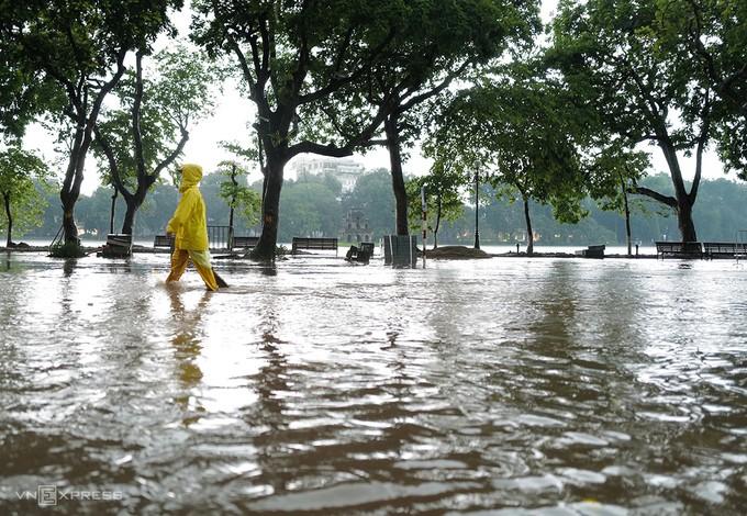 Mực nước hồ Hoàn Kiếm phía trước cửa Bưu điện Hà Nội và tượng đài Lý Thái Tổ mấp mé mặt đường lúc 18h ngày 17/8. Ảnh: Ngọc Thành