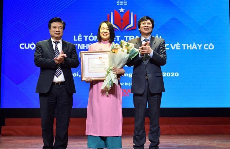 Thứ trưởng GD-ĐT Nguyễn Hữu Độ và Phó Chủ tịch thường trực Hội Nhà báo Việt Nam Hồ Quang Lợi trao giải cho tác giả có tác phẩm đoạt giải nhất. (Ảnh: Nhân Dân)
