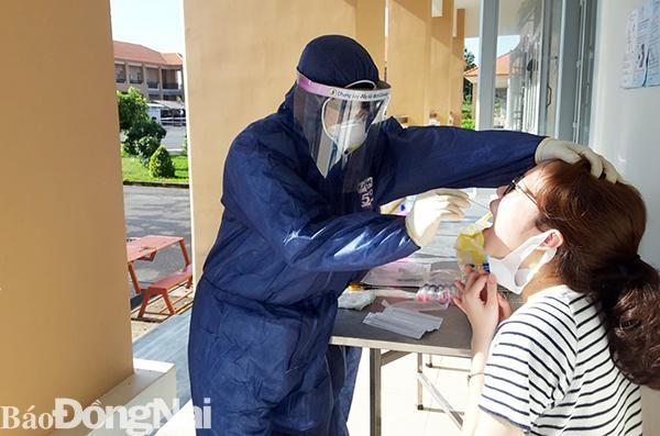 Các bác sĩ quân đội lấy mẫu xét nghiệm và kiểm tra sức khỏe công dân đang cách ly tập trung tại Trung đoàn Đồng Nai. (Ảnh: Báo Đồng Nai)
