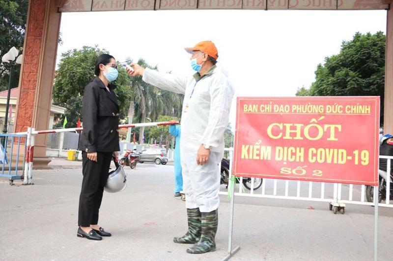Người dân thị xã Đông Triều được kiểm tra thân nhiệt khi đi qua các chốt kiểm soát phòng dịch Covid-19. (Ảnh: Nhân Dân)