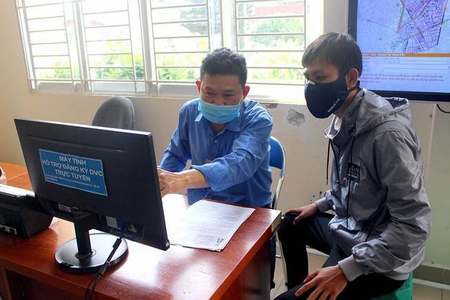 Cán bộ tại bộ phận một cửa quận Bình Tân đang hướng dẫn người dân cách làm thủ tục bằng hình thức trực tuyến. (Ảnh: Lê Thoa/Báo Pháp luật TP HCM)