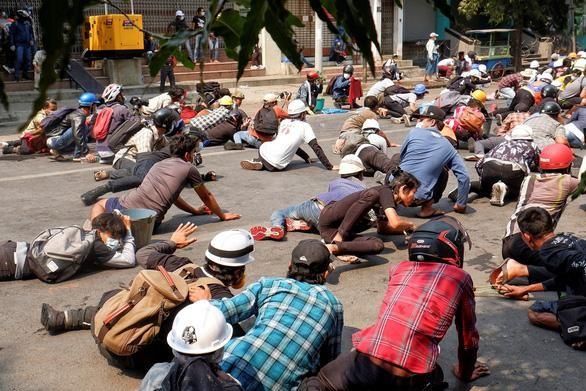Người biểu tình nằm rạp xuống đất khi lực lượng an ninh nổ súng để giải tán đám đông ở Mandalay, Myanmar ngày 3-3 - Ảnh: REUTERS