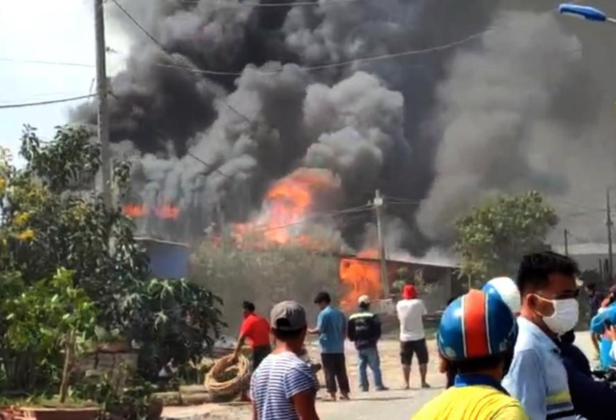 Khói lửa bùng cháy dữ dội bao trùm 3 căn nhà. (Ảnh: TTXVN)