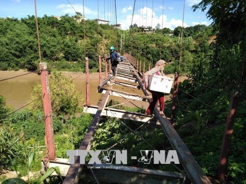 Người dân xã Tam Chung bất chấp tính mạng đi qua cầu để sang sông. (Ảnh: TTXVN)