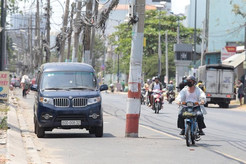 Dãy cột điện nằm dưới lòng đường gây mất an toàn giao thông. Ảnh: A.H.
