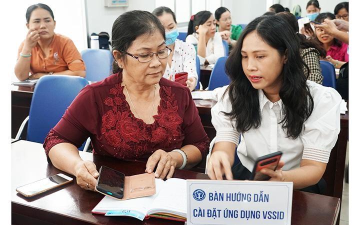 Cán bộ BHXH thành phố Hồ Chí Minh tư vấn, hướng dẫn người dân cài đặt và sử dụng ứng dụng VssID. Ảnh: TRUNG TÂM