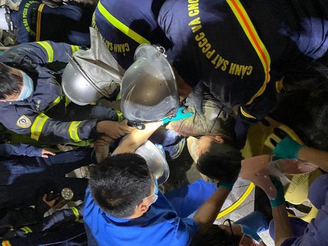 Lực lượng chức năng giải cứu người đàn ông mắc kẹt trong đống đổ nát. Ảnh: Hà Nội mới
