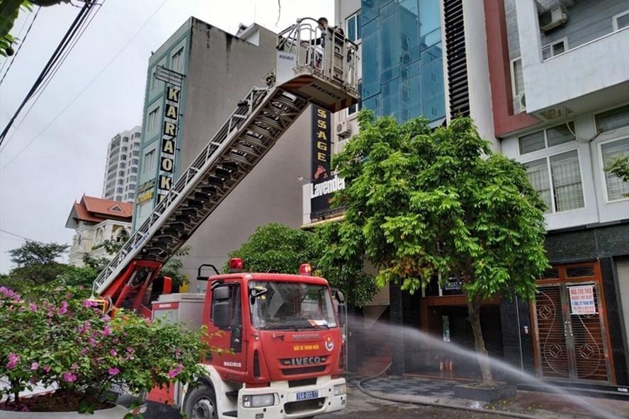 Lực lượng chức năng đang dập lửa và cứu người mắc kẹt bên trong. (Ảnh: Lao Động)