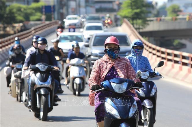 Người dân ra đường cần lưu ý một số biện pháp bảo vệ cơ thể chống lại tác động của tia UV như xoa kem chống nắng, mặc áo dài tay, đeo kính râm. Ảnh: Thành Đạt/TTXVN