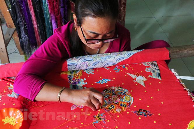 Một nghệ nhân thêu long bào tại làng Đông Cứu. (Ảnh: Báo Văn hoá)