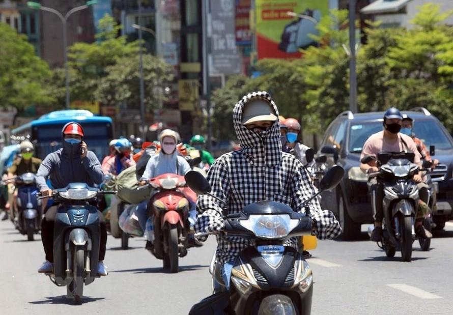 Người dân đi trên đường phải bịt kín để bảo vệ cơ thể dưới cái nắng trên 40 độ C. (Ảnh: Phan Tuấn Anh/TTXVN).