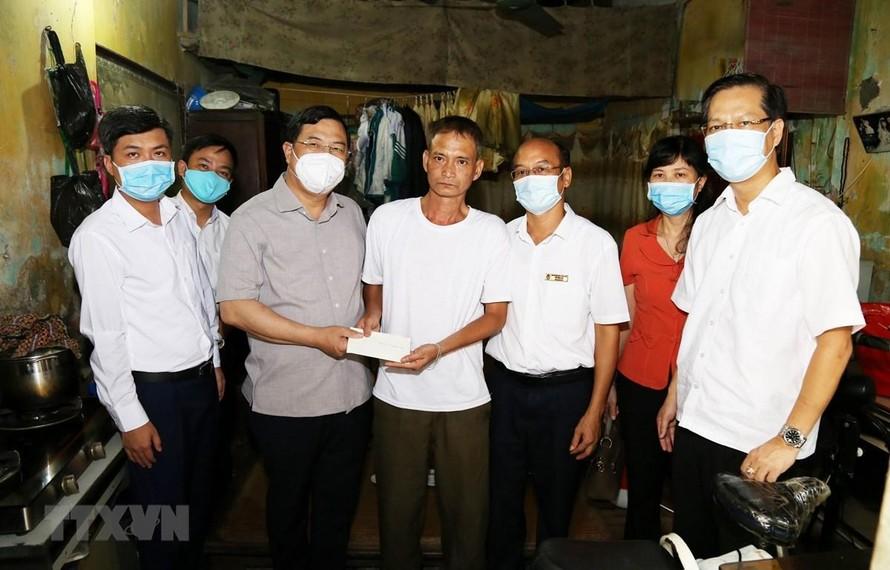 Bí thư tỉnh uỷ Nam Định Phạm Gia Túc trao quà, biểu dương hành động của anh Lương Thanh Hà. (Ảnh: Công Luật/TTXVN)