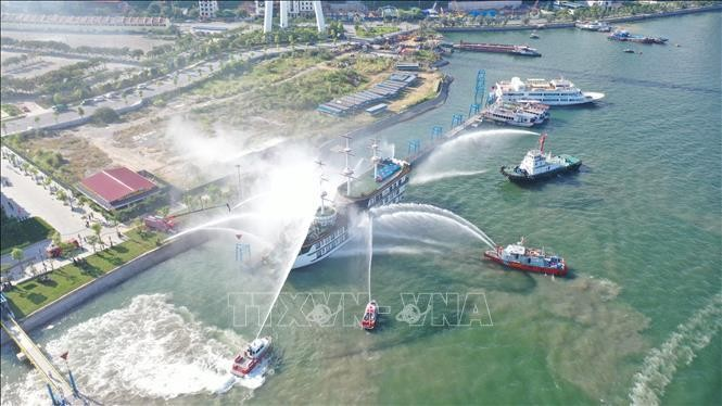 Các tàu tập trung chữa cháy, làm mát tàu bị hỏa hoạn tại buổi diễn tập. (Ảnh: TTXVN)