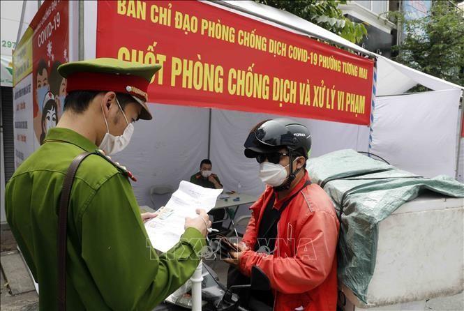 Lực lượng chức năng kiểm tra giấy tờ liên quan người tham gia giao thông tại chốt kiểm soát trên phố Trương Định, quận Hoàng Mai (ảnh chụp sáng 29/7). Ảnh: Trần Việt/TTXVN