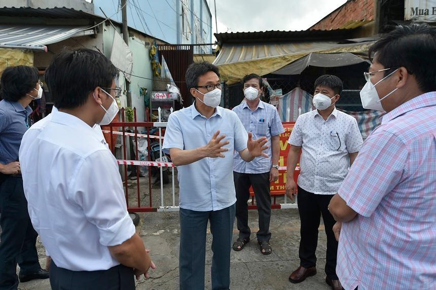 Phó thủ tướng Vũ Đức Đam trao đổi với lãnh đạo quận Bình Tân (TP.HCM) trước một khu nhà trọ công nhân đang bị phong toả, chiều 25/7. Ảnh: VGP.