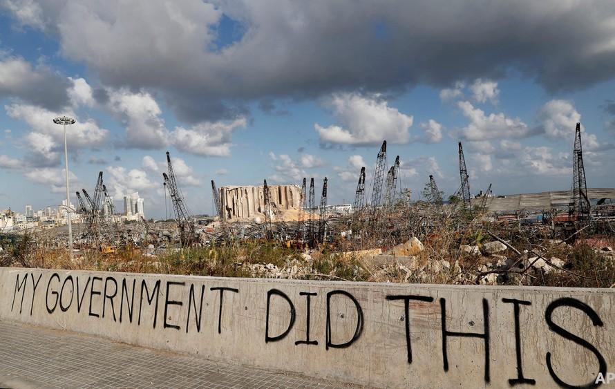 Dòng chữ tố cáo chính phủ Lebanon được viết trên 1 bức tường tại cảng Beirut sau vụ nổ kinh hoàng ngày 4/8/2020. Đắng sau là khung cảnh hoang tàn mà vụ nổ gây ra. (Ảnh: AP)