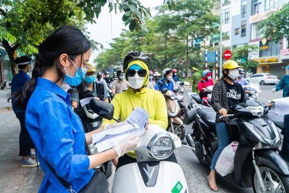 Kiểm tra giấy đi đường tại một chốt kiểm soát COVID-19 ở Hà Nội - Ảnh: PHẠM TUẤN
