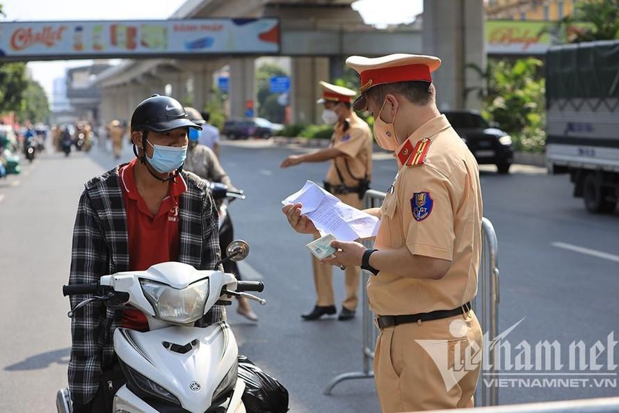 Lực lượng chức năng kiểm tra giấy tờ người dân trên đường Nguyễn Trãi. (Ảnh: Vietnamnet)
