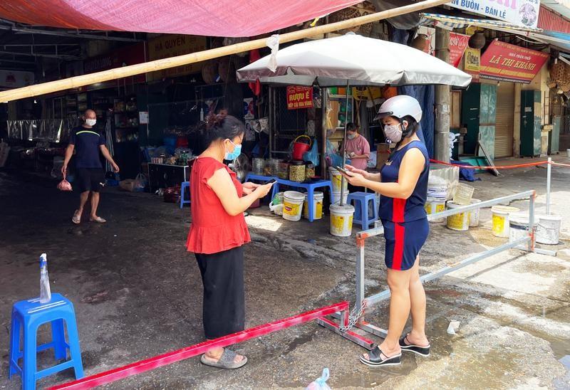 Cổng được chặn bằng khung sắt, nhiều người đi xe đứng ngoài chờ người bán mang hàng ra. Nhiều người chọn phương thức thanh toán qua chuyển khoản nhằm tránh lây lan dịch bệnh. (Ảnh: Kinh tế & Đô thị)