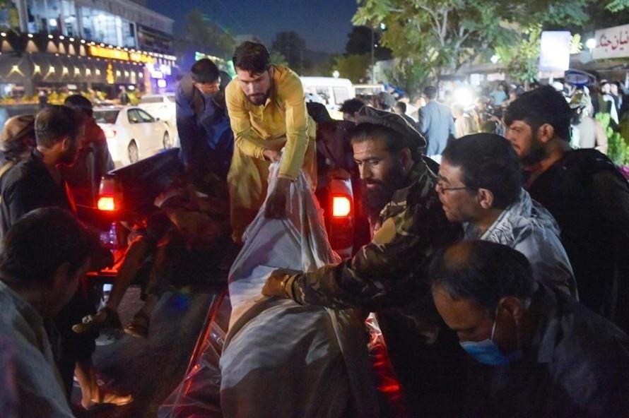 Các tình nguyện viên và nhân viên y tế nâng thi thể từ một chiếc xe bán tải bên ngoài bệnh viện ở thủ đô Kabul sau hai vụ nổ. (Ảnh: VnExpress)