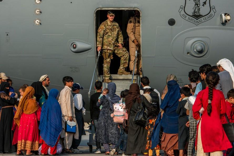 Lính Mỹ chuẩn bị cho người tị nạn Afghanistan lên máy bay tại một căn cứ không quân ở Qatar.