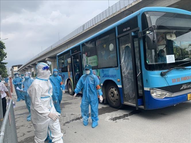 Xe buýt đưa công dân phường Thanh Xuân Trung đi di dời. (Ảnh: TTXVN)