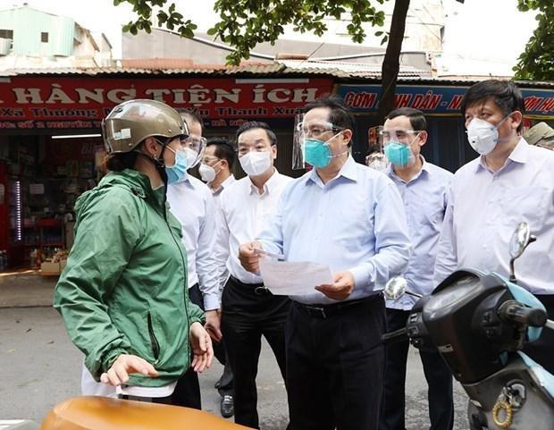 Thủ tướng Phạm Minh Chính kiểm tra giấy phép đi đường và khai báo y tế của người dân trên địa bàn quận Thanh Xuân. (Ảnh: Dương Giang/TTXVN)