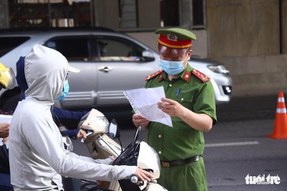 Cảnh sát kiểm tra giấy đi đường của người dân. (Ảnh: Danh Trọng)