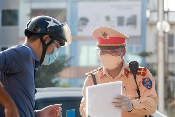 """Cảnh sát giao thông kiểm tra giấy đi đường của người dân từ """"vùng xanh"""" vào """"vùng đỏ"""" ở Hà Nội. (Ảnh: Tuổi trẻ)"""