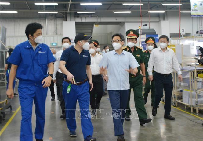 Phó Thủ tướng Chính phủ Vũ Đức Đam thăm, kiểm tra hoạt động sản xuất kinh doanh tại Khu Công nghiệp Linh Trung 1 trong ngày đầu nới lỏng giãn cách xã hội. (Ảnh: TTXVN)