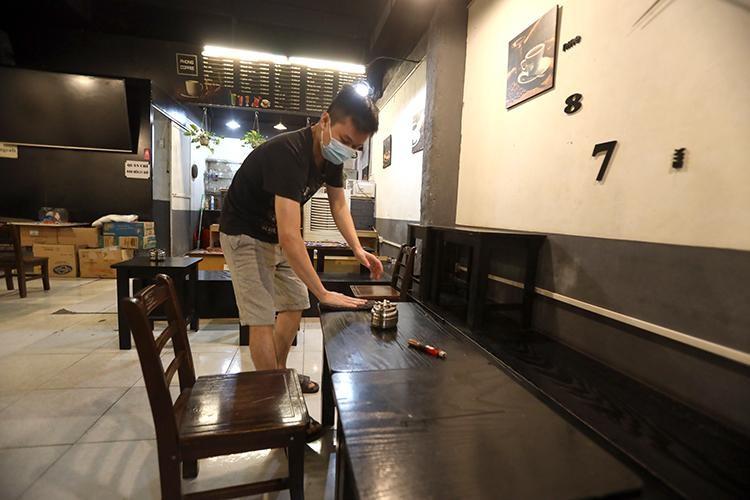 Tại quán cà phê 37 đường Cù Chính Lan (phường Khương Mai, quận Thanh Xuân), khi nghe tin được mở cửa trở lại từ 6 giờ ngày 14/10, anh Thuận chủ quán đã tiến hành dọn dẹp cửa hàng ngay trong tối 13/10. (Ảnh: TTXVN)