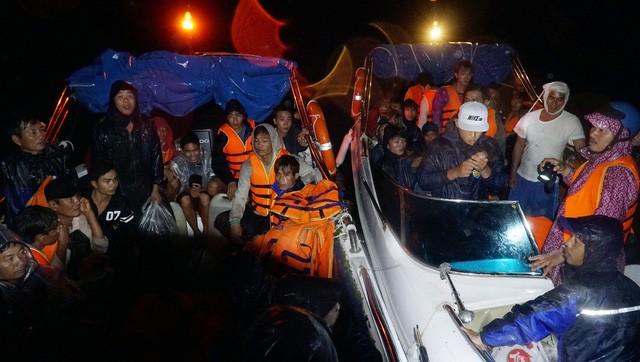 Những ngư dân mắc kẹt được cứu đưa vào bờ - Ảnh: Nam Trần, báo Tuổi trẻ