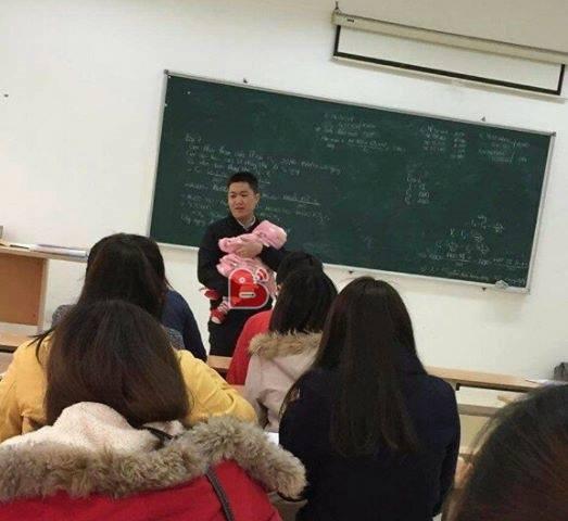 Thầy giáo bế con cho nữ sinh viên làm bài thi thu hút sự chú ý của cộng đồng mạng. Ảnh: beat.vn