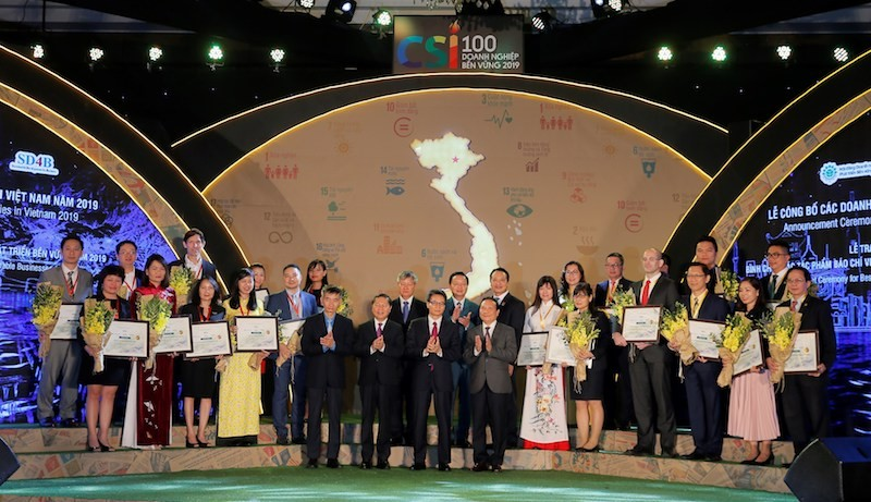 Bà Lê Thị Ngọc Mỹ - Giám đốc Bộ phận PTBV, đại diện HEINEKEN Việt Nam (hàng đầu thứ 3 từ trái sang) nhận giải top 3 DN PTBV nhất (khối sản xuất) năm thứ 4 liên tiếp