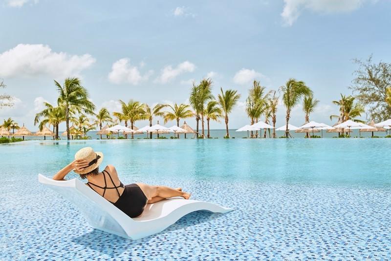 Khách hàng tận hưởng cảm giác thư thái bên bể bơi tuyệt đẹp trong khu nghỉ dưỡng Mövenpick Resort Waverly Phú Quốc