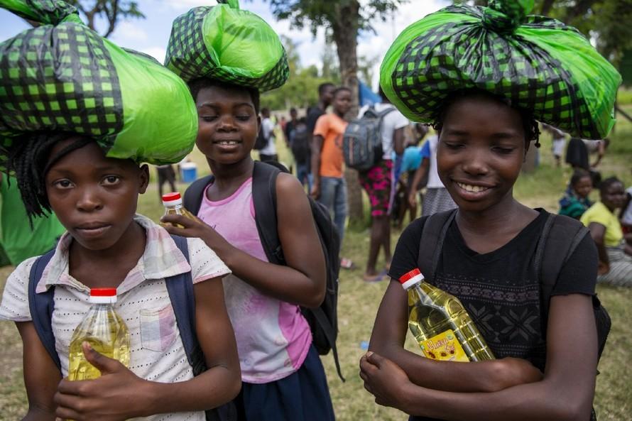 Các nữ sinh ở Beira (Mozambique) lấy khẩu phần ăn về nhà trước khi trường học đóng cửa vào tháng Tư.(Ảnh: Karel Prinsloo/Arete/UN Mozambique).